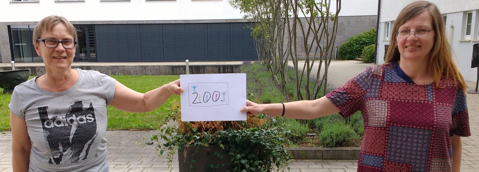 Beide Kirstens halten ein Zettel mit 200 zwischen sich